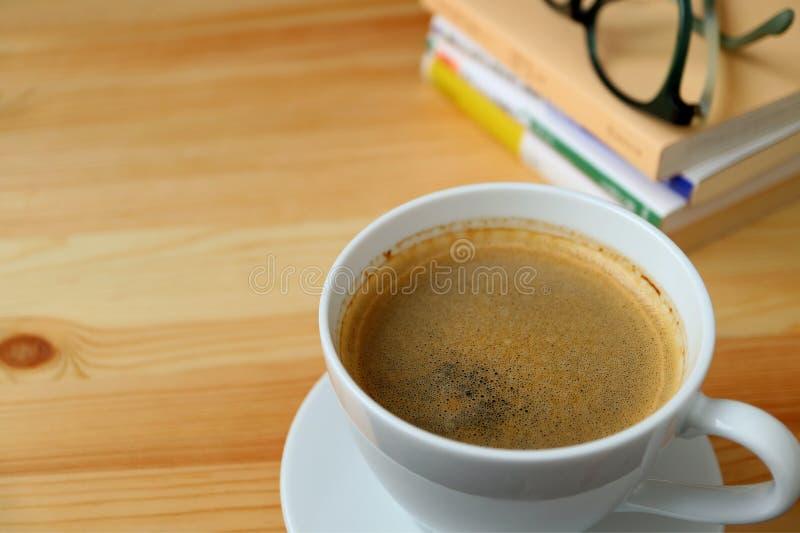 一个杯子与堆的热的咖啡书和玻璃在木桌上 图库摄影