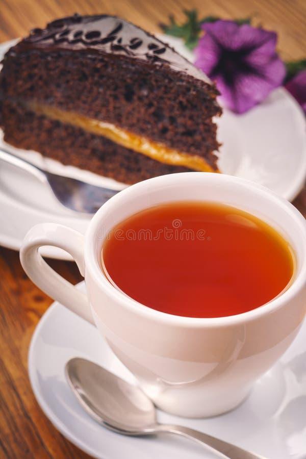 一个杯子与Sacher蛋糕可口片断的新鲜的热的茶在木桌上的 免版税库存图片