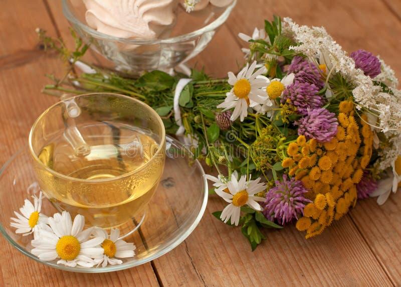 一个杯子在一个玻璃杯子的甘菊茶,碗marsmallows和领域夏天花束开花木表面上 免版税库存图片