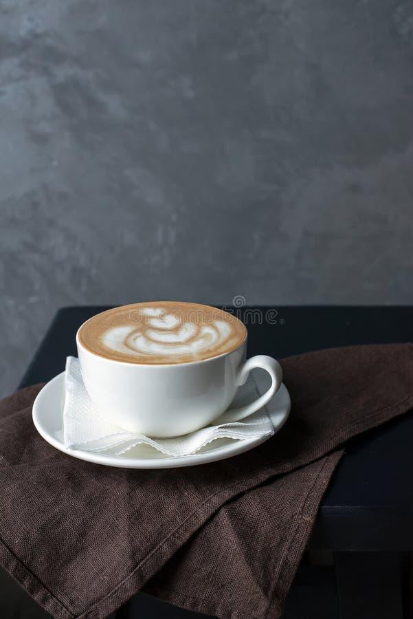一个杯子在一块棕色餐巾的热奶咖啡 库存图片