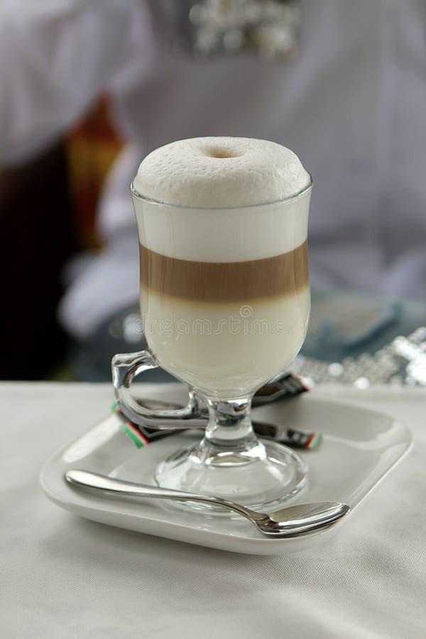 一个杯子在桌上的拿铁macchiato与白色桌布 库存图片