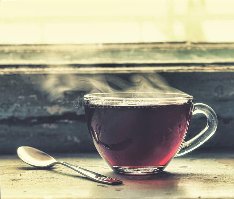 一个杯子在窗口的热的茶 库存照片