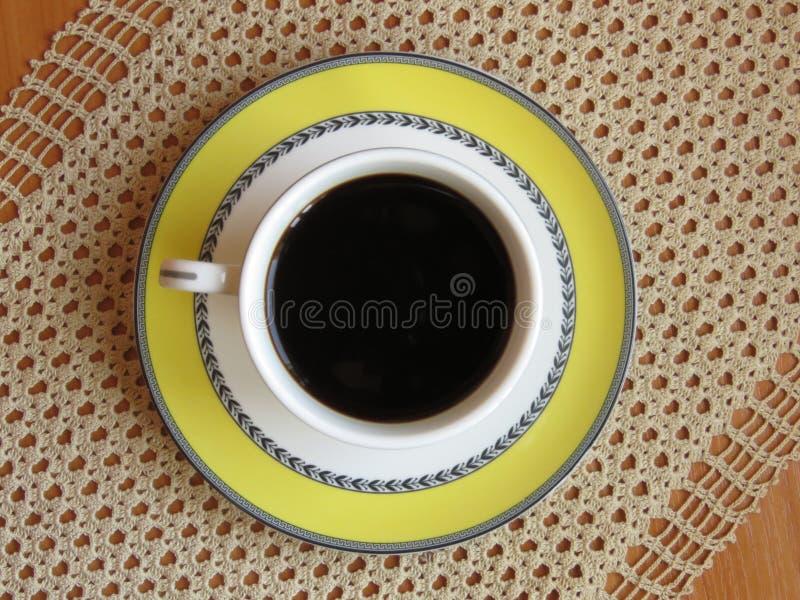 一个杯子在钩针编织桌布和橡木桌背景的黑暗的咖啡 r 库存照片