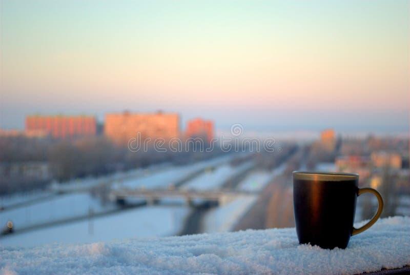 一个杯子在阳台栏杆的热的红茶立场以冷淡的冬天黎明和被弄脏的全景为背景 免版税库存照片