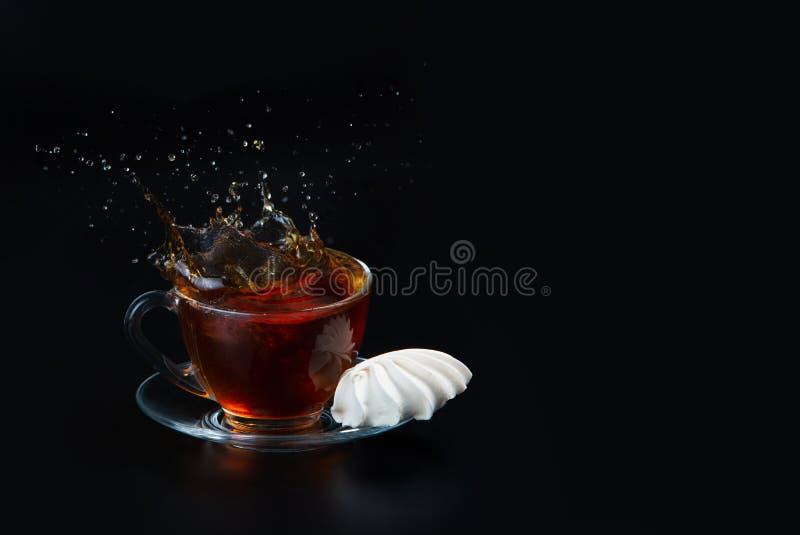 一个杯子在黑被隔绝的背景的红茶 在杯子旁边的蛋白甜饼 ?? ?? 免版税库存图片