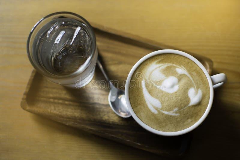 一个杯子拿铁咖啡与一杯水一起供食了,投入在木盘子 免版税库存图片