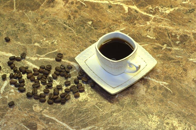 一个杯子无奶咖啡和咖啡豆在一张大理石桌上说谎 r 免版税库存图片