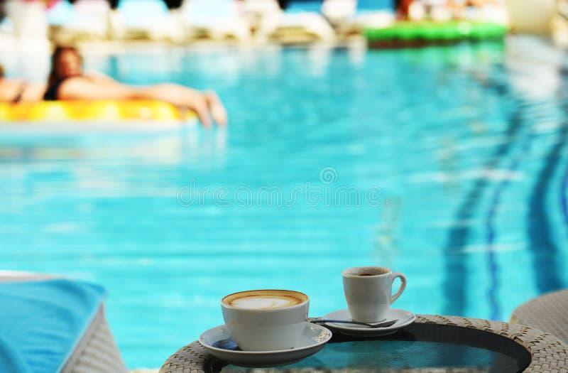 一个杯子热奶咖啡和咖啡在鲜绿色水池水背景  免版税图库摄影
