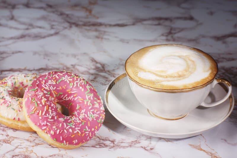 一个杯子热奶咖啡在一张大理石桌上的咖啡立场在两个美丽的油炸圈饼旁边 库存图片