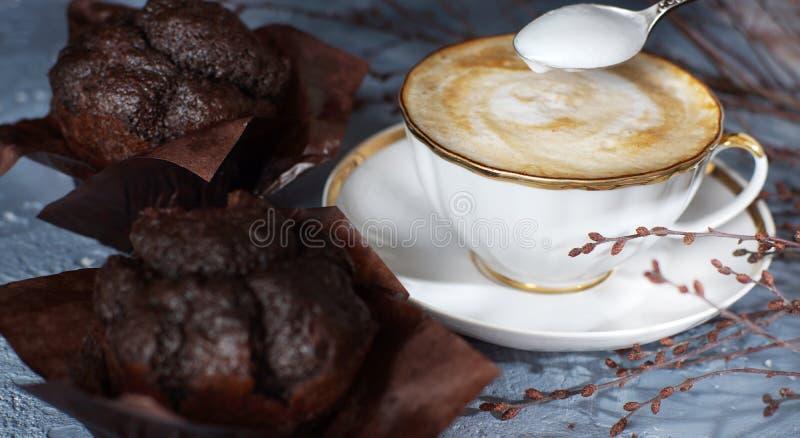 一个杯子热奶咖啡在桌上的咖啡立场在两美丽的巧克力碎片松饼旁边 库存图片