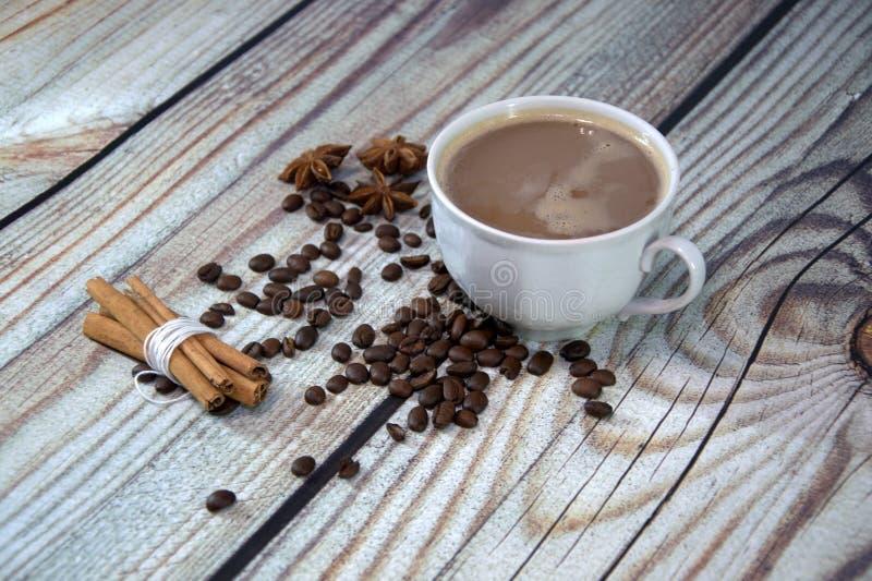 一个杯子热奶咖啡,一束在一张木桌上的桂香、咖啡豆和八角谎言 r 图库摄影