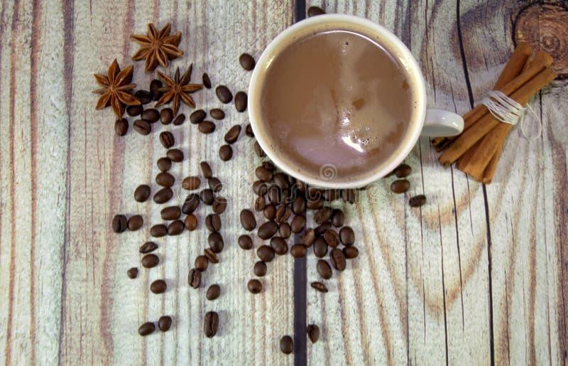 一个杯子热奶咖啡,一束在一张木桌上的桂香、咖啡豆和八角谎言 r 免版税库存照片