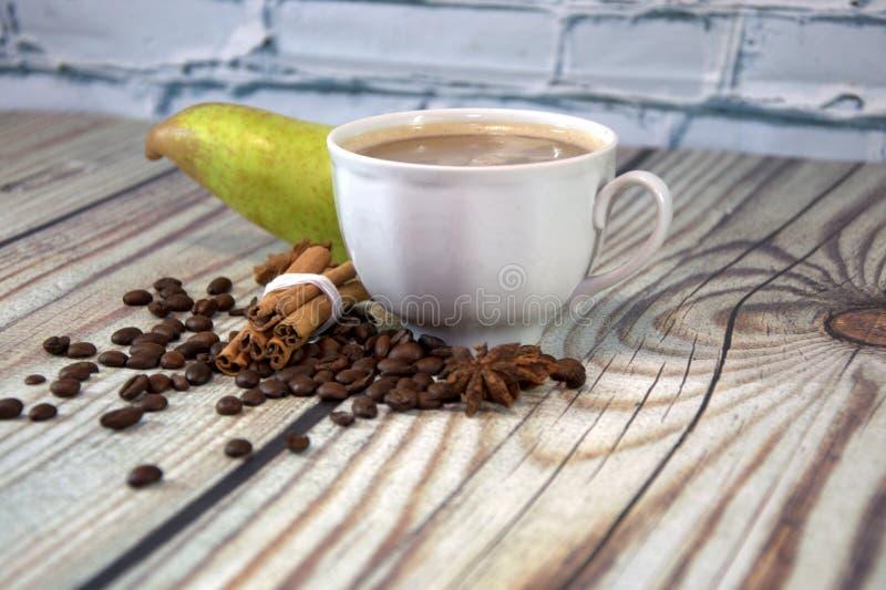 一个杯子热奶咖啡,咖啡豆、一束桂香和梨在一张木桌上说谎对一个白色砖墙 r 免版税库存图片