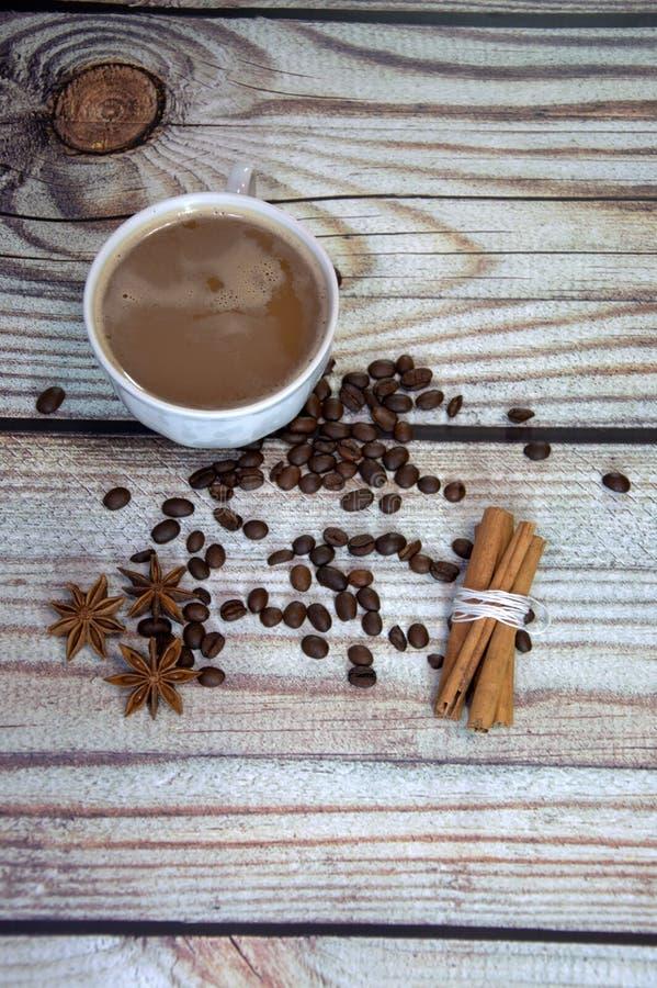 一个杯子热奶咖啡,肉桂条、咖啡豆和星aniseas在一张木桌上说谎 r 库存图片