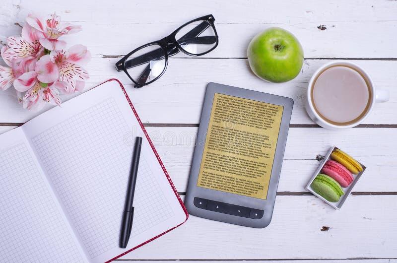 一个杯子热的咖啡、玻璃、一个笔记本和一本e书在木头 免版税库存图片