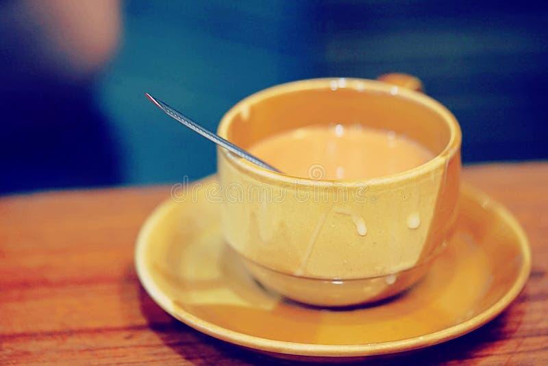 一个杯子热的牛奶茶,在一个棕色杯子的热的饮料在木桌上有模糊的背景 图库摄影
