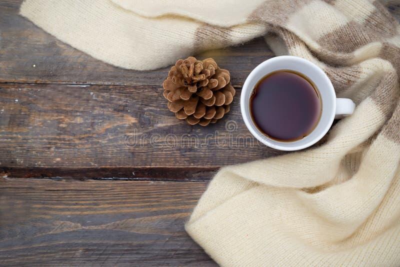 一个杯子热的茶和在木背景的一条温暖的围巾 平的l 库存照片