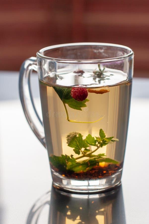 一个杯子的静物画从草本的茶在有反射的一瓷砖 草莓叶子和莓果在杯子浮动 免版税库存图片
