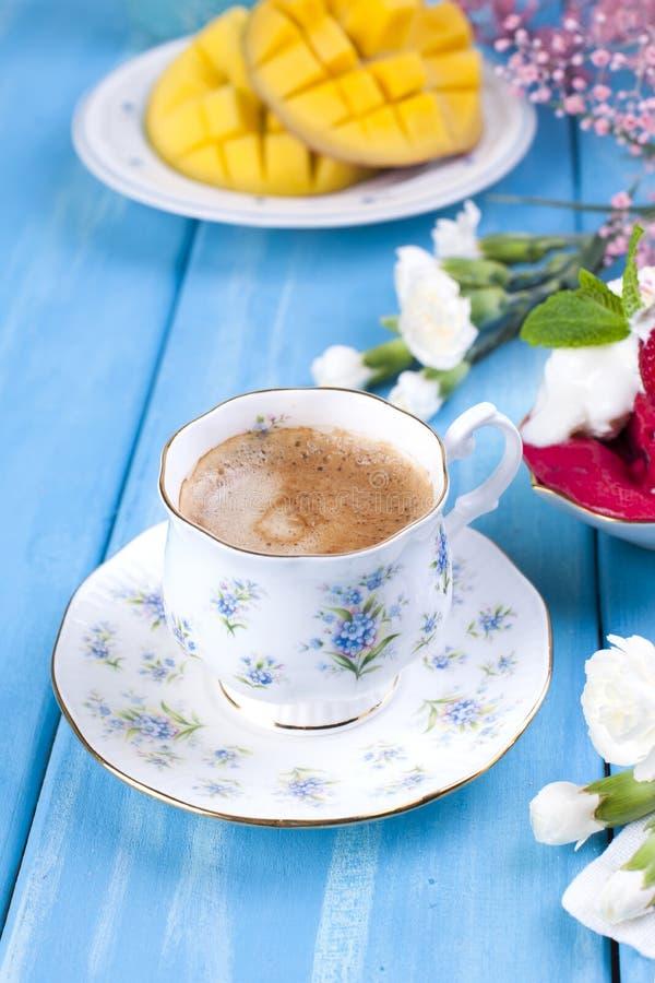 一个杯子芬芳早晨咖啡,果子和花是白色和桃红色在蓝色木背景 抽象背景同类的照片结构葡萄酒 复制空间 免版税库存图片