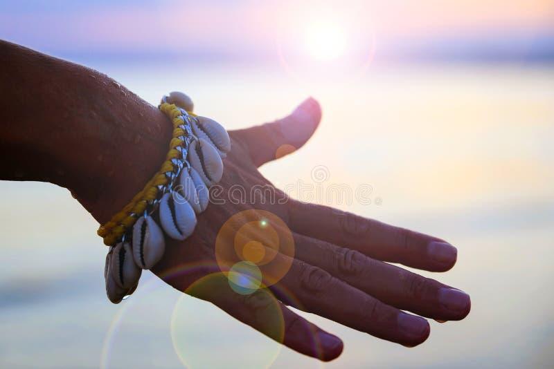 一个柔和的女孩的手的特写镜头有镯子的由贝壳做成 在水背景  在日落背景的现有量 库存照片
