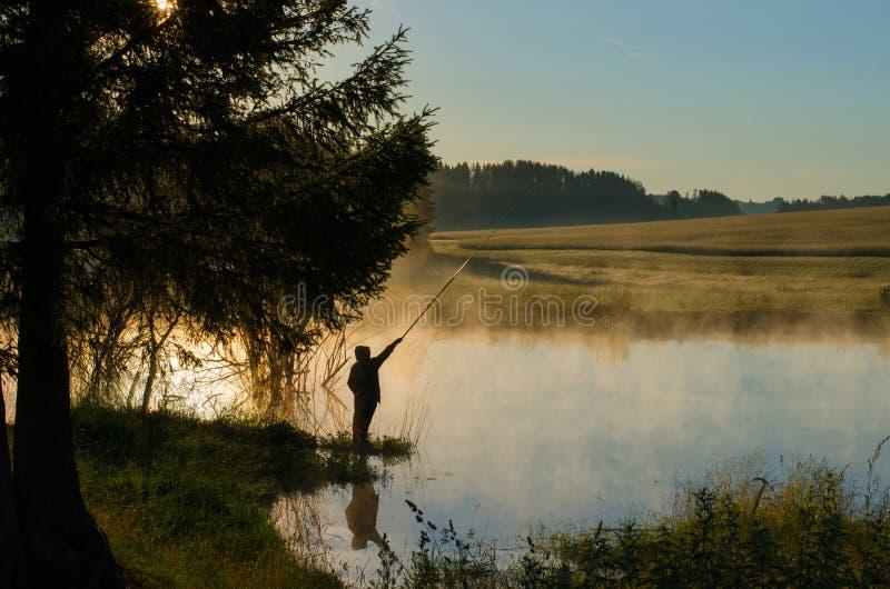 一个树木繁茂的湖的一位渔夫雾的 免版税库存照片
