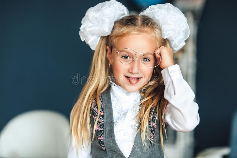 一个校服的女孩有玻璃的显示舌头 她在她的手上拿着一个统治者 她获得乐趣,当依靠桌在时 免版税库存照片