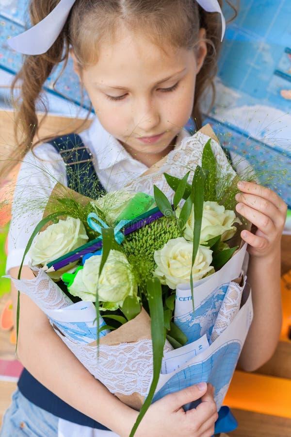 一个校服的美丽的女孩在与花束的一个校务委员会附近在手上 免版税图库摄影