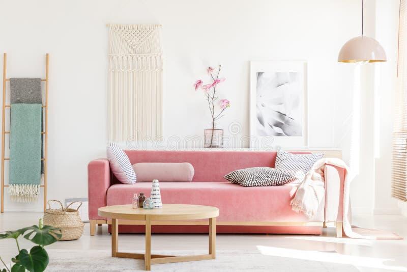 一个桃红色沙发的真正的照片有坐垫和一揽子常设beh的 图库摄影