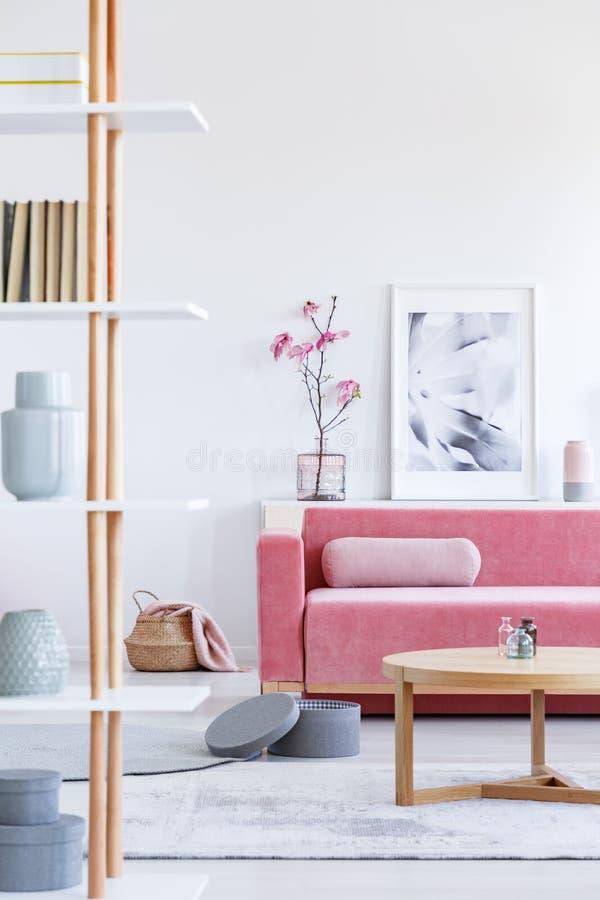 一个桃红色沙发的真正的照片有站立在woode后的坐垫的 库存图片