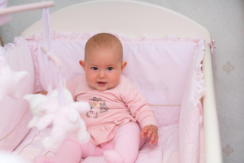 一个桃红色轻便小床的逗人喜爱的矮小的女婴 图库摄影