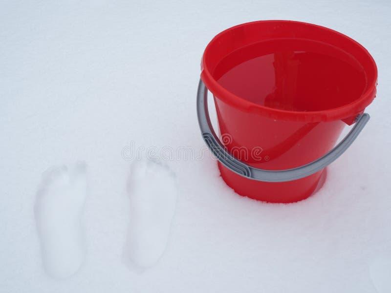 一个桶在雪的水 库存图片