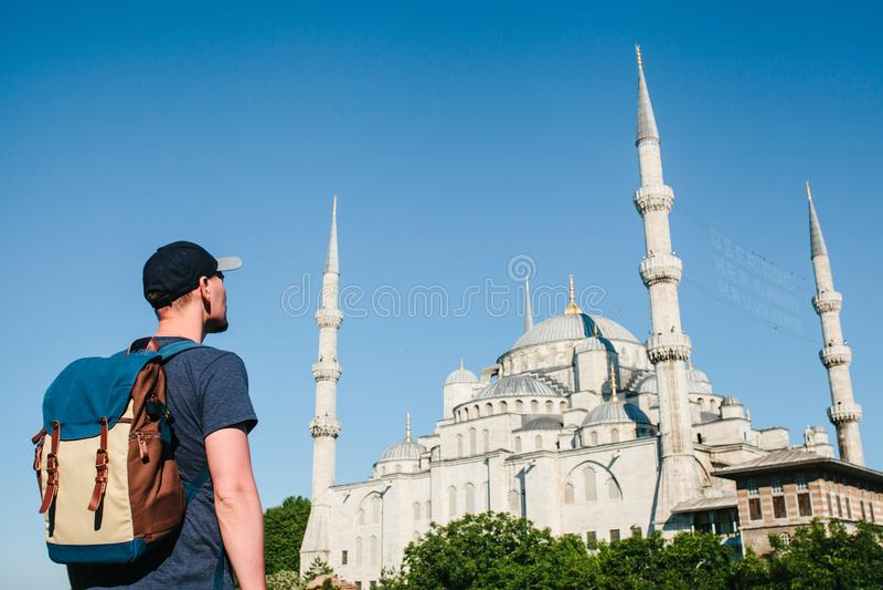 一个棒球帽的一个人有在蓝色清真寺旁边的一个背包的是著名视域在伊斯坦布尔 旅行,旅游业 库存图片