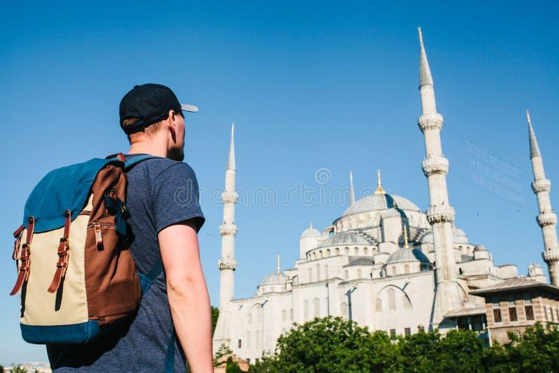 一个棒球帽的一个人有在蓝色清真寺旁边的一个背包的是著名视域在伊斯坦布尔 旅行,旅游业 库存照片