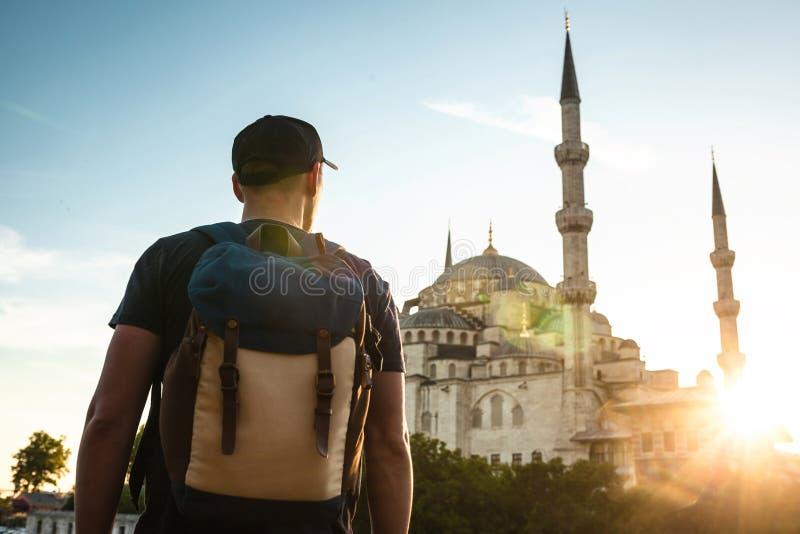 一个棒球帽的一个人有在蓝色清真寺旁边的一个背包的是著名视域在伊斯坦布尔 旅行,旅游业 免版税库存图片