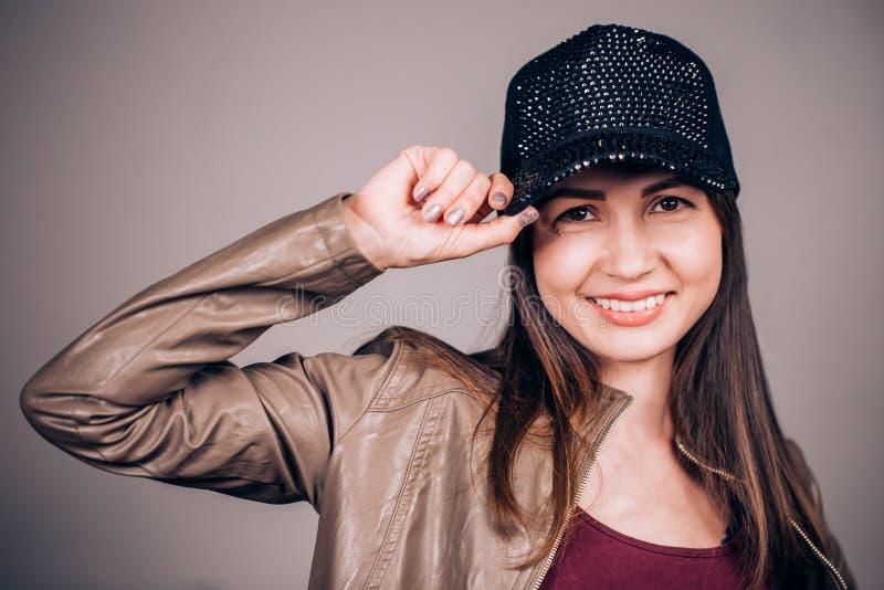 一个棒球帽的一名可爱的年轻深色的妇女有看照相机的微笑的 情感面孔,幸福,喜悦概念 免版税库存照片
