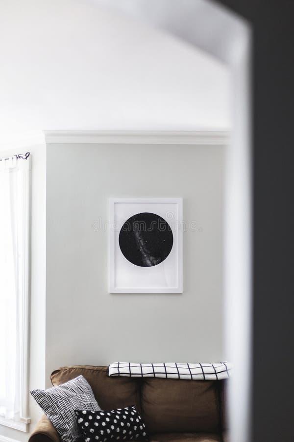一个棕色沙发的垂直的射击有枕头的和在一个框架的一张黑白图片在墙壁上 图库摄影