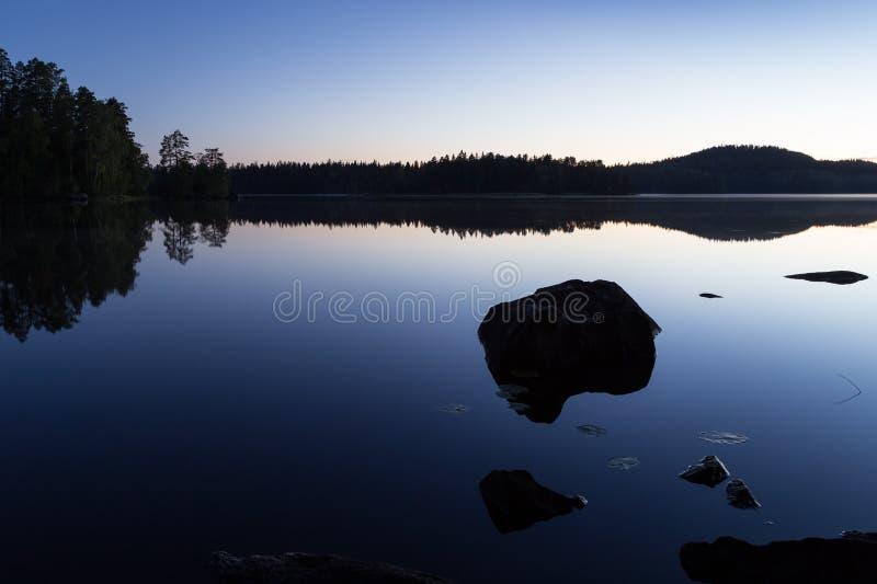 一个森林和岩石的剪影和反射在湖 库存图片