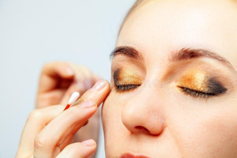 一个模型的眼睛的构成的特写镜头与一张淡色的面孔的,化妆师在他的手上拿着一根棉花棒和 免版税库存图片