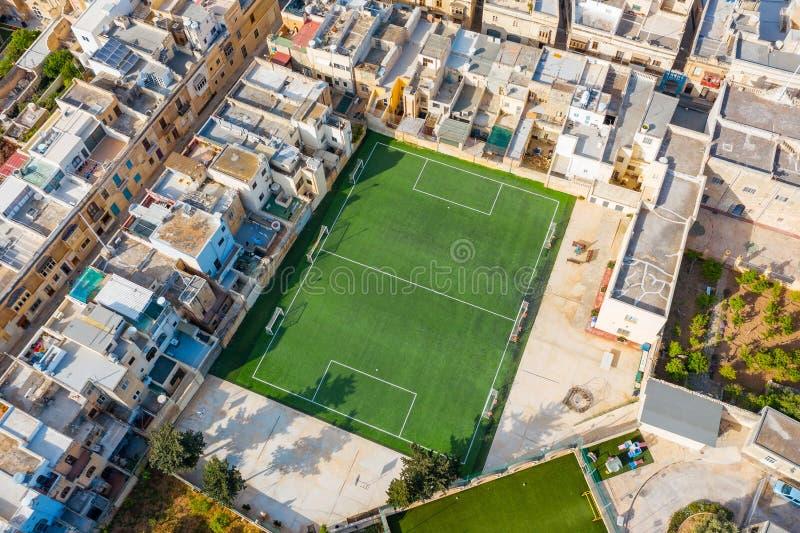 一个橄榄球场的鸟瞰图在一个住宅区,在石房子中在城市 免版税库存照片