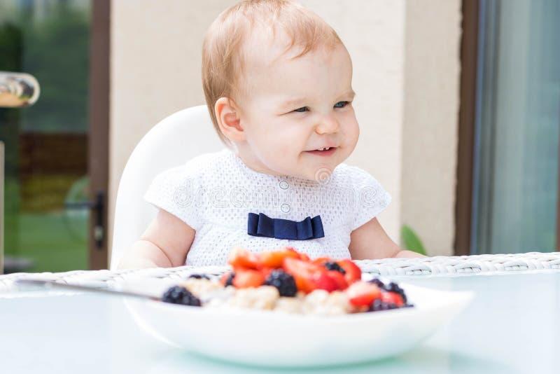 一个正在蹒跚学步的小女孩坐在一张粥前的桌子旁,手里拿着浆果 免版税库存图片