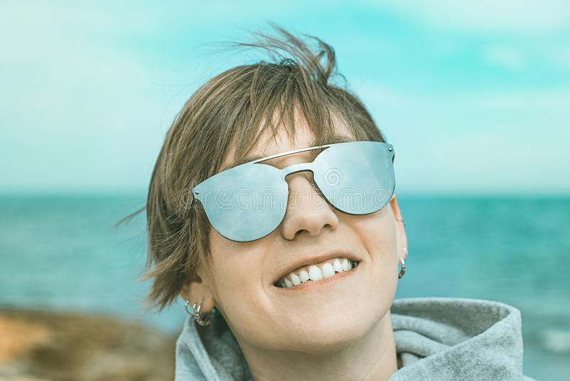 一个正常女孩的画象有微笑的太阳镜的在海滩 库存照片