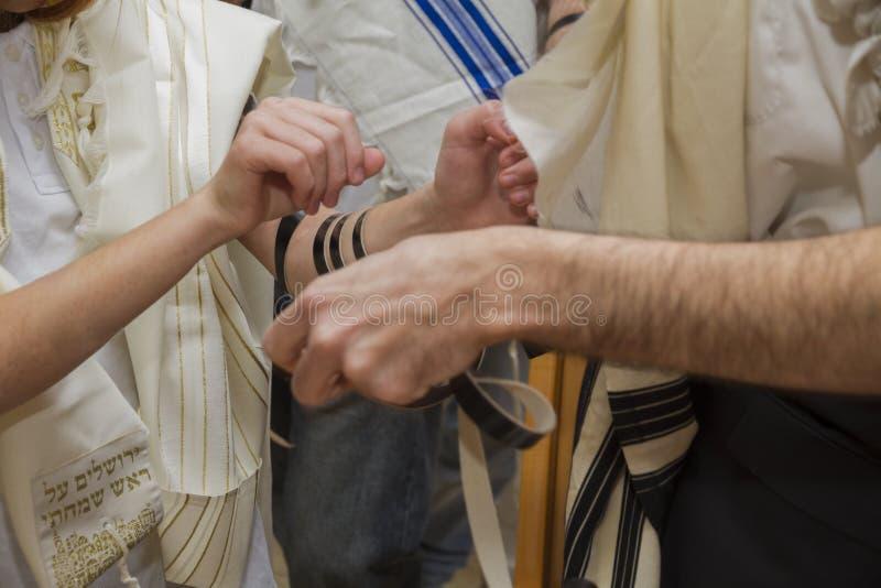 一个正统人,佩带的晨祷披巾,在A年轻人胳膊投入了犹太Tefillin为祈祷做准备 图库摄影