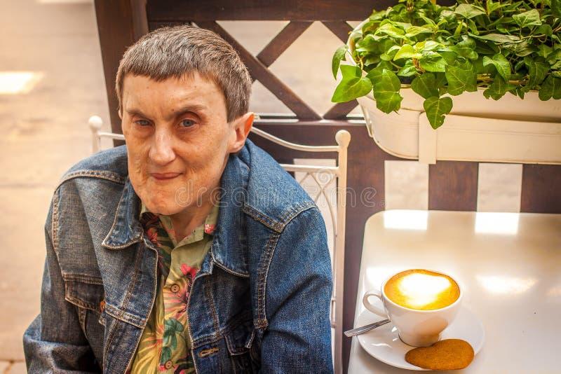 一个残疾人坐在一个室外咖啡馆 库存图片