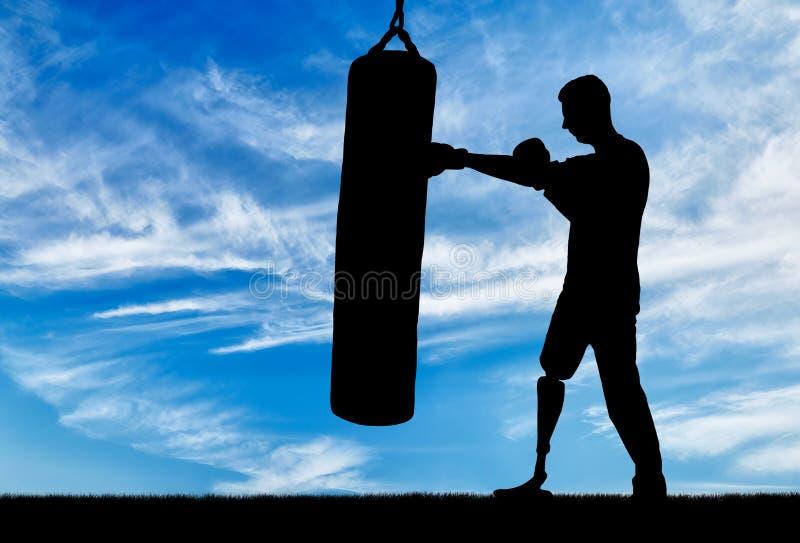 一个残疾人的剪影有腿假肢的,训练与一个沙袋 免版税库存图片