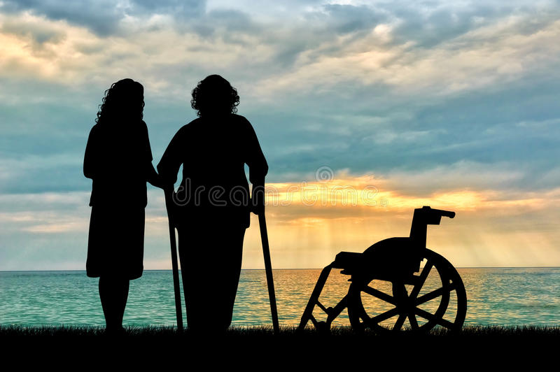 一个残疾轮椅的剪影在偷窥者和近的海附近的 一个残疾人和家的概念老人的