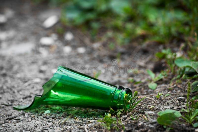 一个残破的绿色玻璃瓶的脖子在街道上说谎 免版税库存图片