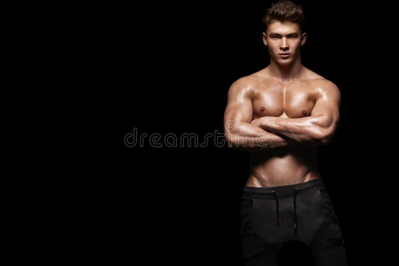 一个残酷和适合人爱好健美者的特写镜头画象 黑背景的运动员爱好健美者 库存照片
