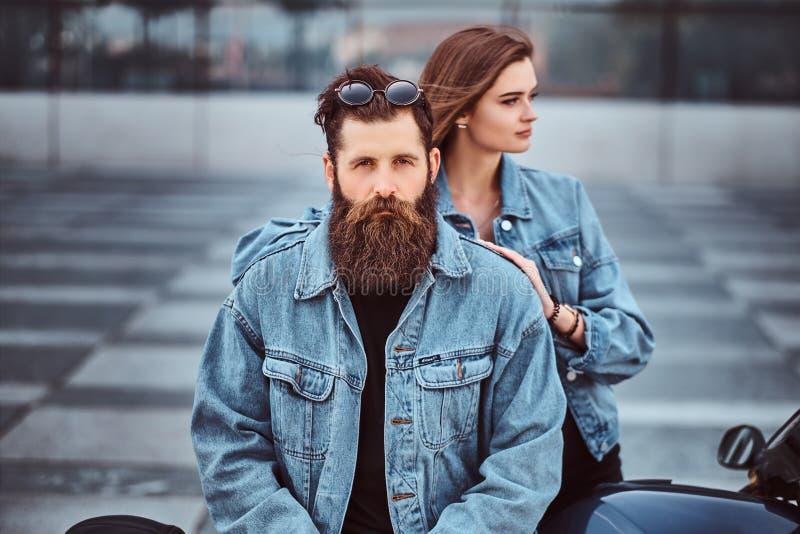 一个残酷有胡子的男性和他的女朋友的行家夫妇的特写镜头画象在牛仔裤夹克穿戴了反对 库存照片