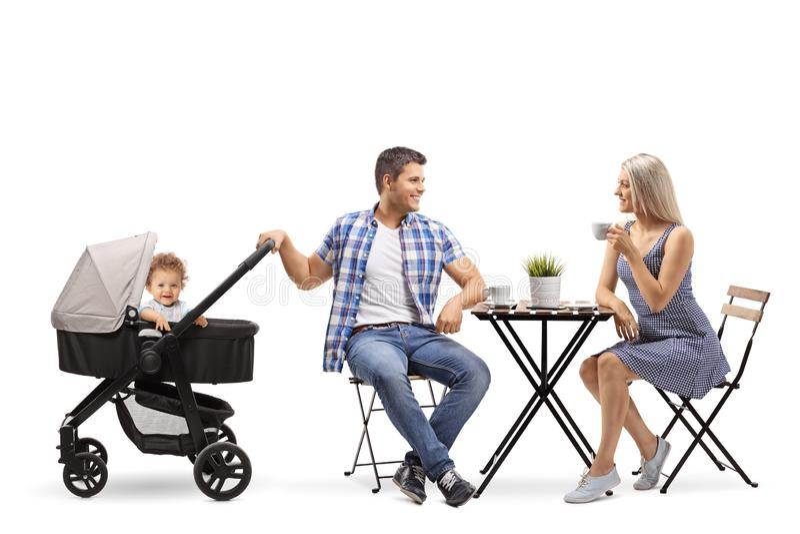 一个母亲、父亲和一个婴孩的年轻家庭婴儿推车sittin的 免版税库存照片