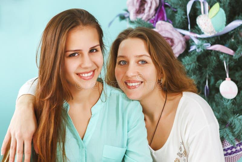 一个母亲的画象有在家拥抱在附近的青少年的女儿的 免版税库存照片